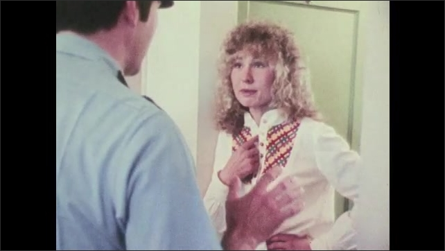 1970s: UNITED STATES: police officer talks to lady in house. Angry lady talks with police man in home.