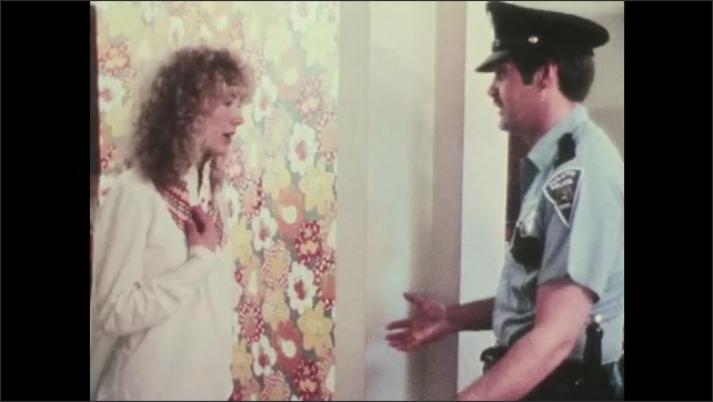 1970s: UNITED STATES: lady talks to police officer in front room of home. Officer speaks with lady in house