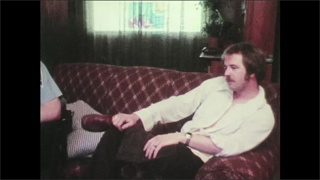 1970s: UNITED STATES: angry man sits on sofa next to police man. Couple talk with police