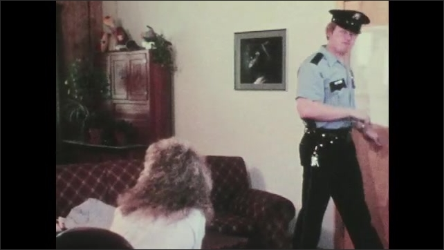 1970s: UNITED STATES: police officers talk to lady in house. Lady sits on chair. Man puts on hat. Officers leave home. Lady sits on chair upset
