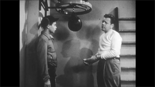 1950s: UNITED STATES: man hits punch bag. Boy talks to man in gym. Man gives gloves to boy. Boy hits punch bag