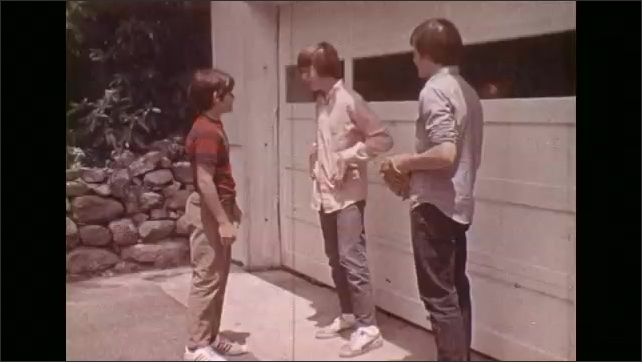 1970s: Boy speaks. Boy attempts to open garage door. Boy argues. Boys shove and fight one another. Third boy attempts to break up fight. Red car pulls into driveway followed by group of kids.