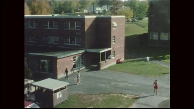 1970s: People mingle outside of building, throw Frisbee back and forth. People walk in and out of building.