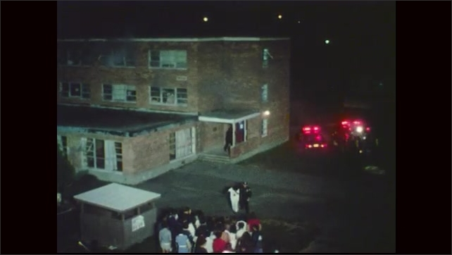 1970s: Smoke billows from window. Police escort people out of building. Trucks with flashing lights sit near building. People gather across from building.