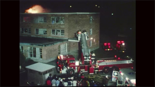 1970s: People gather in group across from building. Smoke and flames on top of building. People wave towels out window. Firemen raise ladder on Fire Truck, swivel ladder towards building.