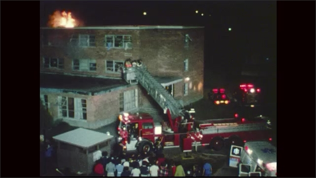 1970s: People gather in group across from building. Smoke billows from windows, flames burn on top of building. Firemen lower truck ladder towards ground.