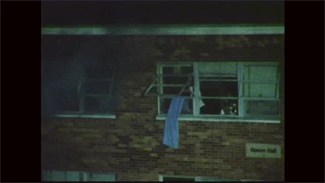 1970s: People gather in group across from building. Smoke billows from windows. People point to window. Person waves towel from window.