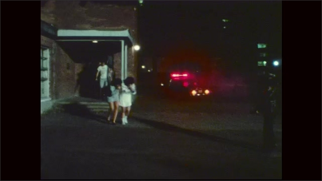 1970s: UNITED STATES: students leave building. Boy on crutches leaves burning building
