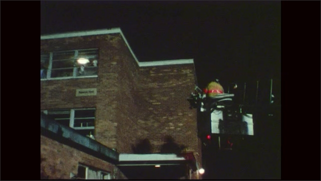 1970s: Building on fire.  Man frantically waves towel out of window.  Fireman in ladder bucket.