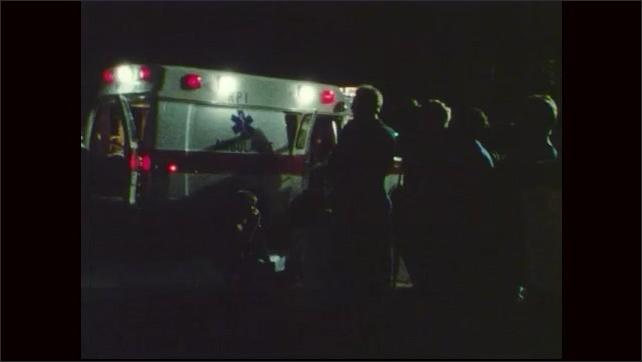 1970s: Burning building.  Smoke.  Ambulance.  Crowd of people.  Men hug.