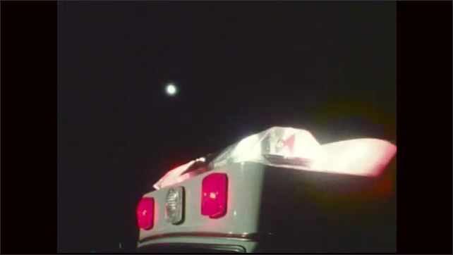 1970s: Flashing lights on fire truck and ambulance.