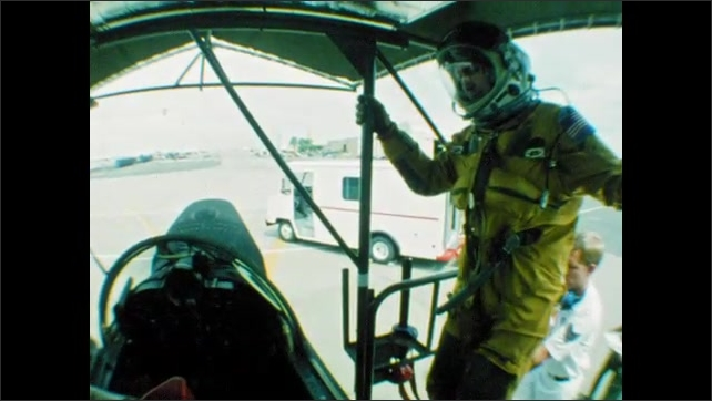 1980s: UNITED STATES: slow motion of man climbing steps in space suit. Man wears altitude suit. Man climbs into seat of plane.
