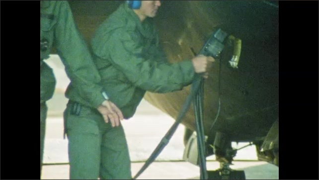 1980s: UNITED STATES: men close hatch on plane. Man removes fuel pipes from plane. Back up pilot sits in vehicle. Man waves plane