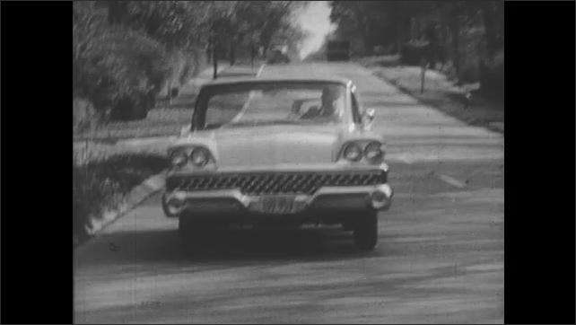 1950s: Man drives down street.  Ball rolls into road.