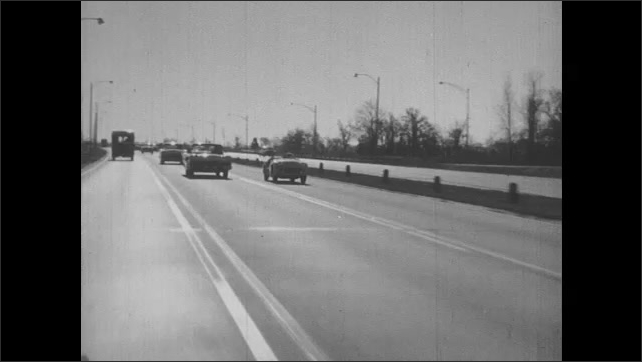 1950s: Man frowns.  Foot presses accelerator.  Tire spins.  Speedometer.  Cars race down highway.  Men look at each other.  Car drives over lane markings.