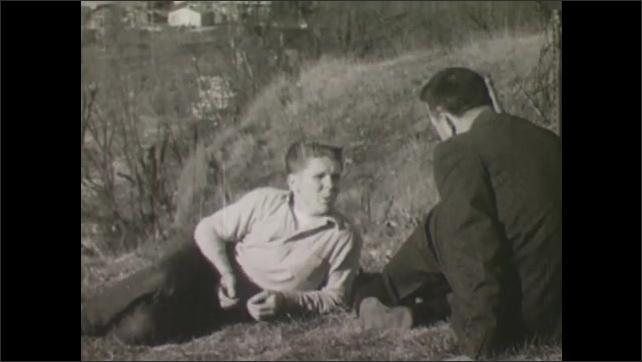 1960s: teenage boy laying on hill talking to older man