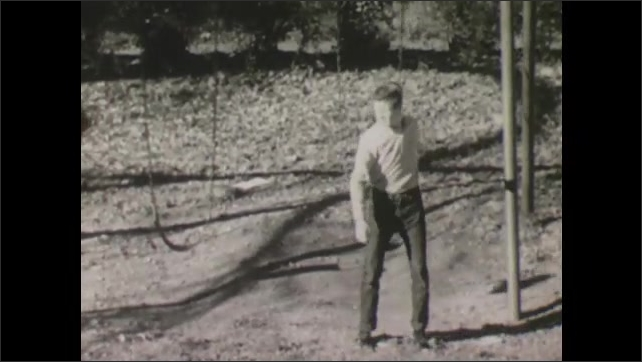 1960s: teenage boy getting on swings in school playground then walking over to a pole