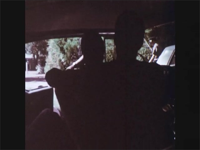 1960s: patrol vehicle with lights and siren blocks country road as police officers step out, put on hat, approach passenger car and talks to men and women in seats through open doors.