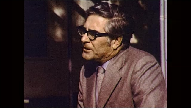 1970s: Man in glasses and suit sits outdoors and speaks.