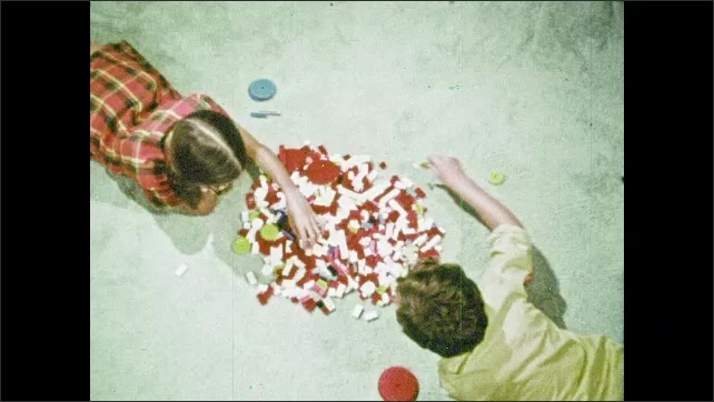 1970s: Boy and girl lie on carpet and sort Legos from pile.