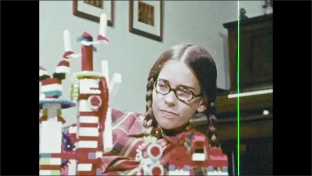 1970s: Hand steadies blocks of Lego contraption. Girl speaks. Hand attaches Legos. Girl talks. Boy checks gears and blocks.