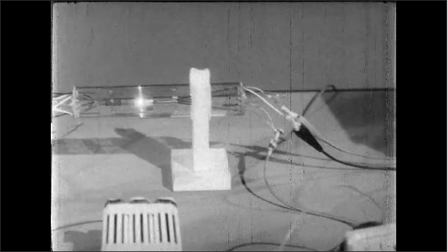 1960s: Needle on thermocouple meter. Hand throws switch on table. Milliamperes meter on table. Needle moves on thermocouple meter.