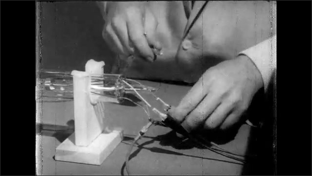 1960s: Scientist points to cylinder apparatus and speaks. Hands uncouple wires and reconnect them to thermocouple meter.