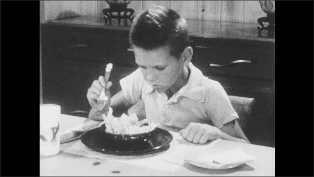 1950s: Man and woman eat dinner at table. Family eats dinner at dining room table. Boy sets down fork and stares at food. Man watches boy in silence.