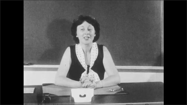 1950s: Teacher sits at desk and speaks to class. Children sit and listen to teacher. Teacher addresses the class. Children sit upright and attentive at desks in classroom.