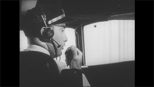 1950s: UNITED STATES: lady speaks on telephone. Pilot sits in plane. Pilot speaks on radio. Workers type at switchboard