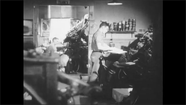 1940s: Close up, boys open door. Men working at machines in printing press, tracking shot through room. Low angle view, man at machine.