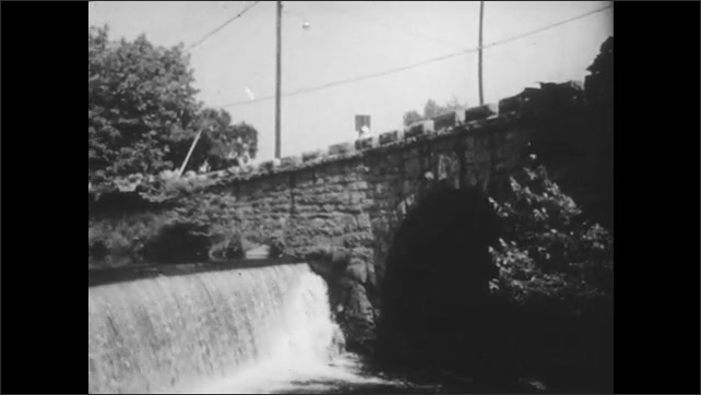 1940s: Long shot, boy gets on bike, rides down street. Boy rides bike across bridge, pan across bridge and waterfall. Boy rides toward house, throws paper  on steps.