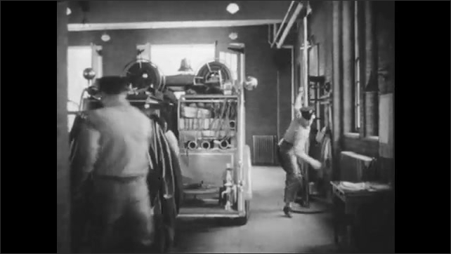 1940s: Boy opens box, pulls alarm. Close up of bell. Men running in fire station. Low angle view, men slide down pole. Close up, man yelling. Feet put on boots.