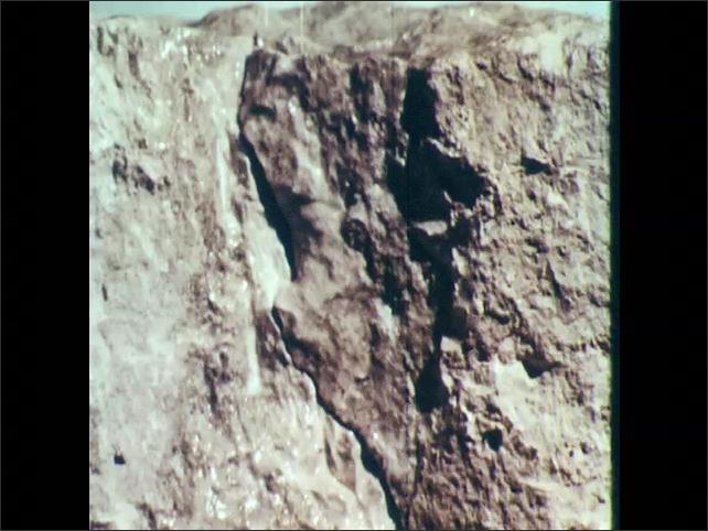 1960s: Waves roll across small rocks. Water falls on rock face, fissure splits open, rock breaks away, crumbles.