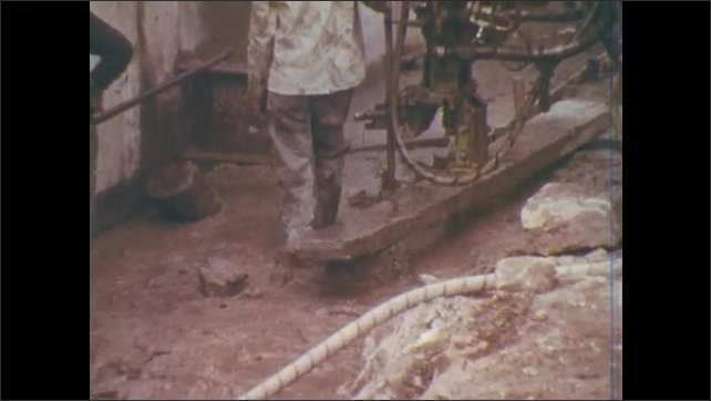 1970s:Battleship bucket moves and dumps earth. Two construction workers stand by drill in a pit.