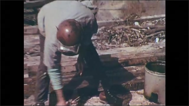 1970s: Construction workers walk towards steel tube. Worker smears brown substance on to  tube with his hand. Workers sign name Poole and Zellman on tube. Welder lights blowtorch.