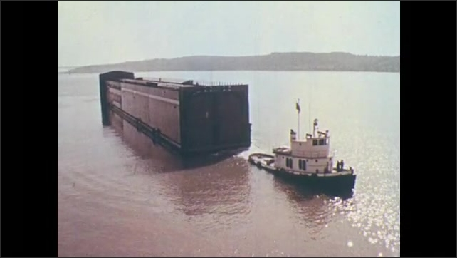1970s: Tugboat tows steel structure into middle of water. Construction crew watches from bank. Tugboat pushes steel structure into river. Drill boat sits on water.