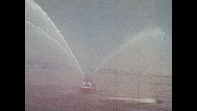 1970s: Tugboats depart at night. Fire boat sprays water in daytime at New York Harbor. Three tugboats guide steel tunnel structure into harbor.