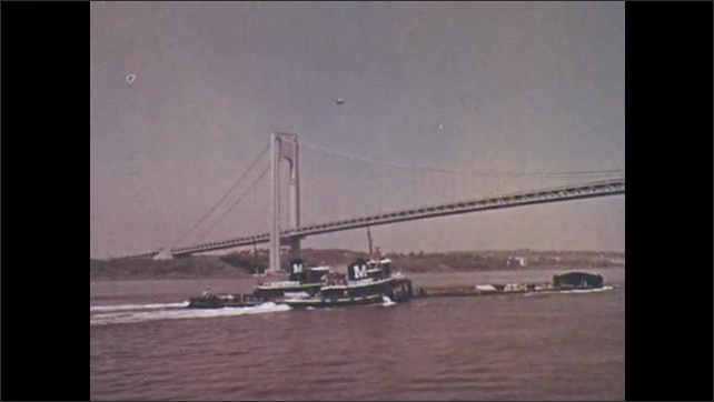 1970s: Politician speaks into microphone. Two tugboats guide tube under the Verrazano Bridge. Helicopter flies above bridge.