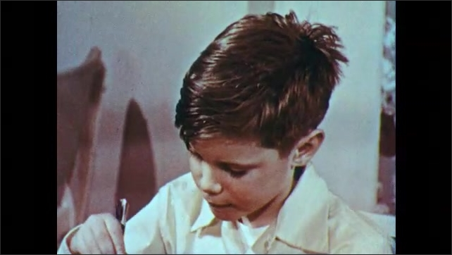 1950s: UNITED STATES: boy drinks glass of milk at table. Boy speaks at table. Boy eats dinner.