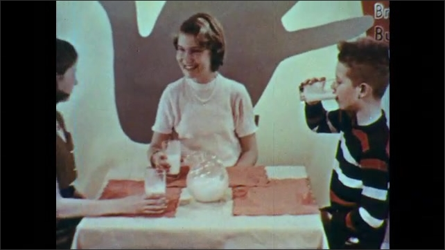 1950s: UNITED STATES: milk and cheese label. Boy drinks glass of milk. Girl drinks milk