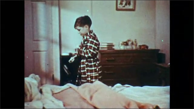 1950s: UNITED STATES: boy points at hand. Boy picks up candy bar. Boy stops and thinks to self