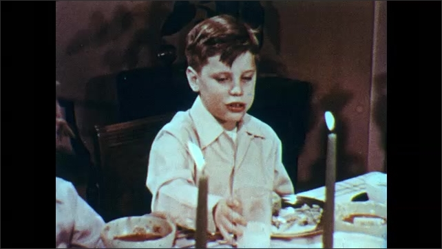 1950s: UNITED STATES: boy counts on fingers before bed. Boy drinks glass of milk. Boy eats meal with family at table