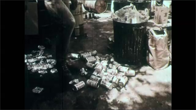 1970s: Recycling center.  Women dump box of bottles into metal can.  Man crushes can with foot.