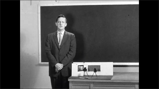 1950s: Man stands in front of blackboard and small diorama of soundstage. Talent speaks on set in soundstage. Man holds clapboard in hands and speaks.