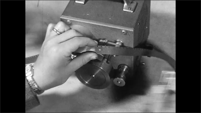 1950s: Hands scrub audio tape back and forth in editing machine. Hand with hole punch cuts dot into frame of soundtrack. Hands remove audio tape.