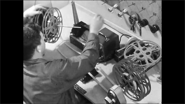 1950s: Man looks into viewfinder of moviola. Man loads reels of film and audio tape onto the editing machine at workbench. Man adds spacers between reels on rewind of editing machine.