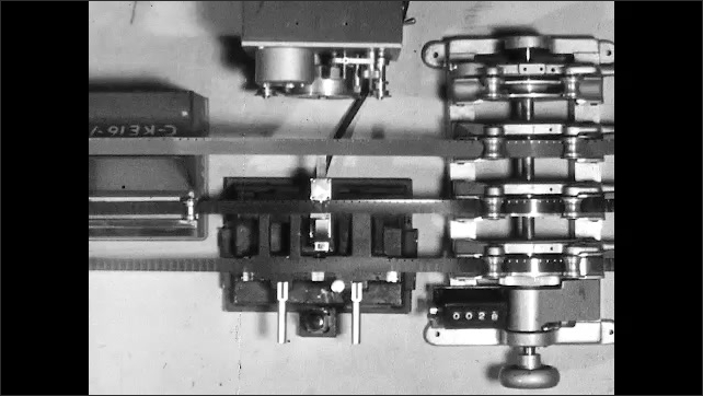 1950s: Hand with pencil marks film in viewer. Tape and film feeds through editing machine and gang synchronizer. Hand with pencil marks cuts on film in gang synchronizer.