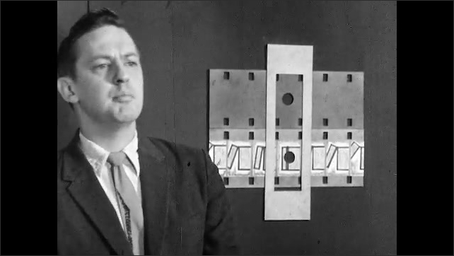 1950s: Man attaches example of film and sound tape to blackboard. Man places cardboard slit over example on blackboard and speaks. Man holds up clap board and speaks.