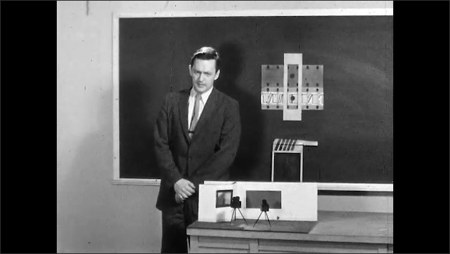 1950s: Man leans clapstick against blackboard and speaks. Hand points to dots on film and audio frame example. Man speaks and exits soundstage.